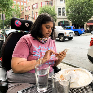 Brown skinned woman with dark brown hair. Wearing a magenta T-shirt. Sitting in a wheelchair at a table with a glass and empty plate. She is looking into her camera phone and typing something.